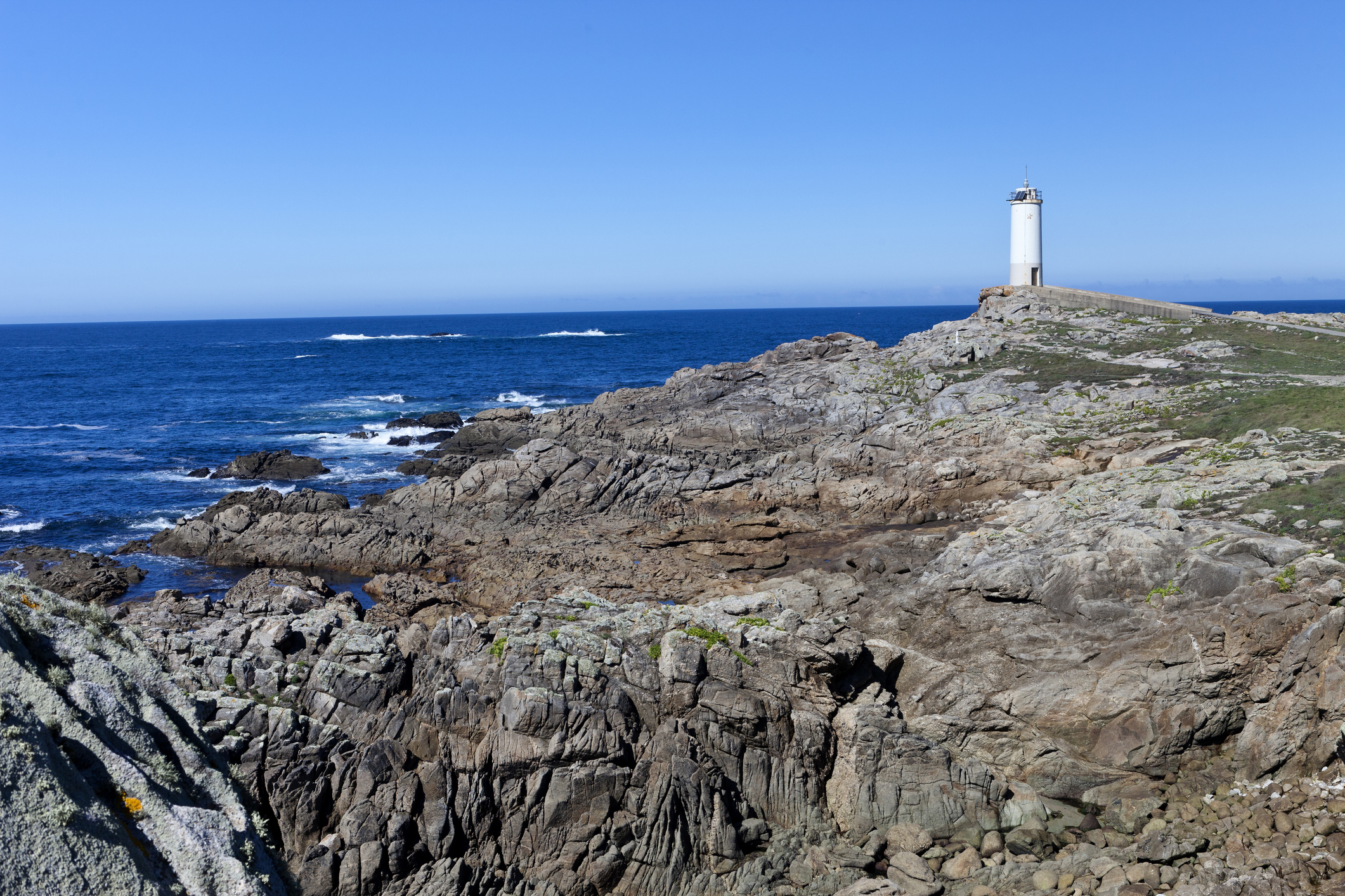 Roncudo lighthouse and white memorial cross in memory of those who died in the Atlantic ocean waters stands near Corme, Costa da Morte (Coast of Death), at A Coruna province (Spain).